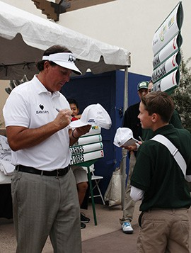 Phil Mickelson signs Will Clayton's ,13, hat after his first round of the Waste Management Phoenix Open to thank Clayton for his help.