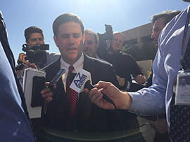 Gov. Doug Ducey leaves an Arizona Board of Education meeting on Monday after saying he wants a review of the state's version of the Common Core standards.