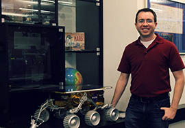 Jonathan Hill, a graduate student in Arizona State University's School of Earth and Space Exploration, stands next to a model of the Sojourner Mars rover.