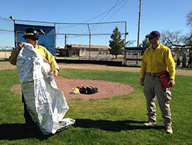 Scott Robb, right, battalion chief with Golder Ranch Fire District, which serves communities north of Tucson, works with firefighter Ryan Hoffman to lead training on deploying heat-resistant fire shelters.