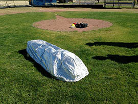 A firefighter lies beneath a fire shelter during a recent training session for southern Arizona firefighters held in Oracle.