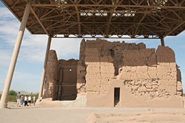 Visitors examine the large earthen house at Casa Grande Ruins National Monument. A lighter area on the wall at bottom left shows plastering that's needed to maintain the structure.