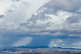 A cumulonimbus cloud produces a shaft of rain. Some say Arizona can help address its water challenges by seeding clouds to produce more rain and snow.