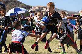 A member of the Kinght Saints jumps in the air as he tries to elude members of the Scruggs Raiders after making an interception. Concussions in tackle football have led to more and more parents signing their kids up for flag football leagues, such as PrimeTime Athletics, which oversees teams such as the Raiders and Saints.